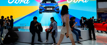 In this April 25, 2018, file photo, attendees visit the Ford booth during Auto China 2018 show held in Beijing, China. China's government says it will postpone planned punitive tariffs on U.S.-made automobiles and other goods following an interim trade deal with Washington.Sunday, Dec. 15, 2019's announcement came after Washington agreed to postpone a planned tariff hike on $160 billion of Chinese goods and to cut in half penalties that already were imposed.